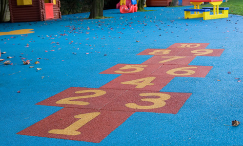 Red wet pour hopscotch in blue playground flooring